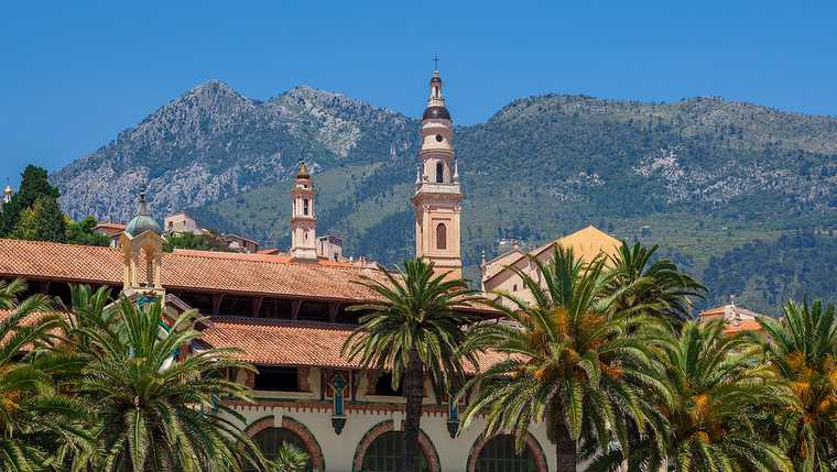 architecture; azur; belfry; bell; blue; campanile; church; city; cote; europe; european; france; french; landmark; menton; mountain; nobody; palm; red; resort; riviera; roof; sky; tile; tourism; tourist; touristic; tower; town; travel;
